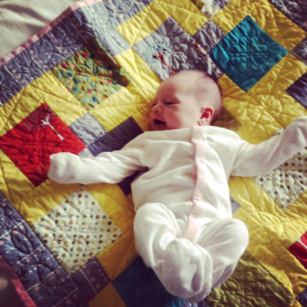 Ara on the beautiful quilt her Grandma W made for her